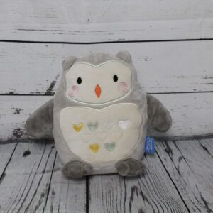 A grey and white cuddly owl sitting on some wooden floor