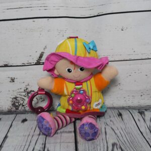 A colourful doll sitting against a wooden background