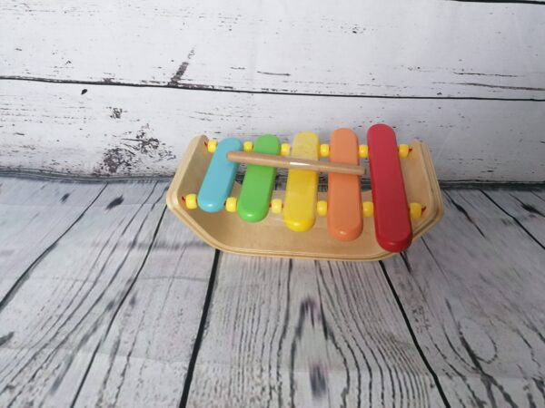 A wooden toy xylophone with rainbow keys